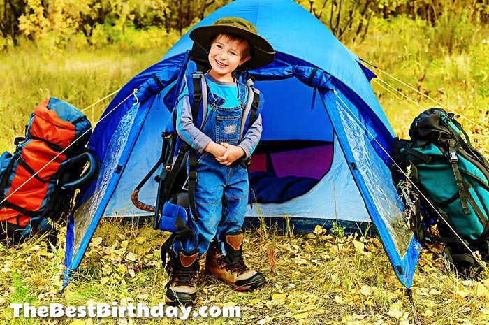 Boy by tent  at camping party